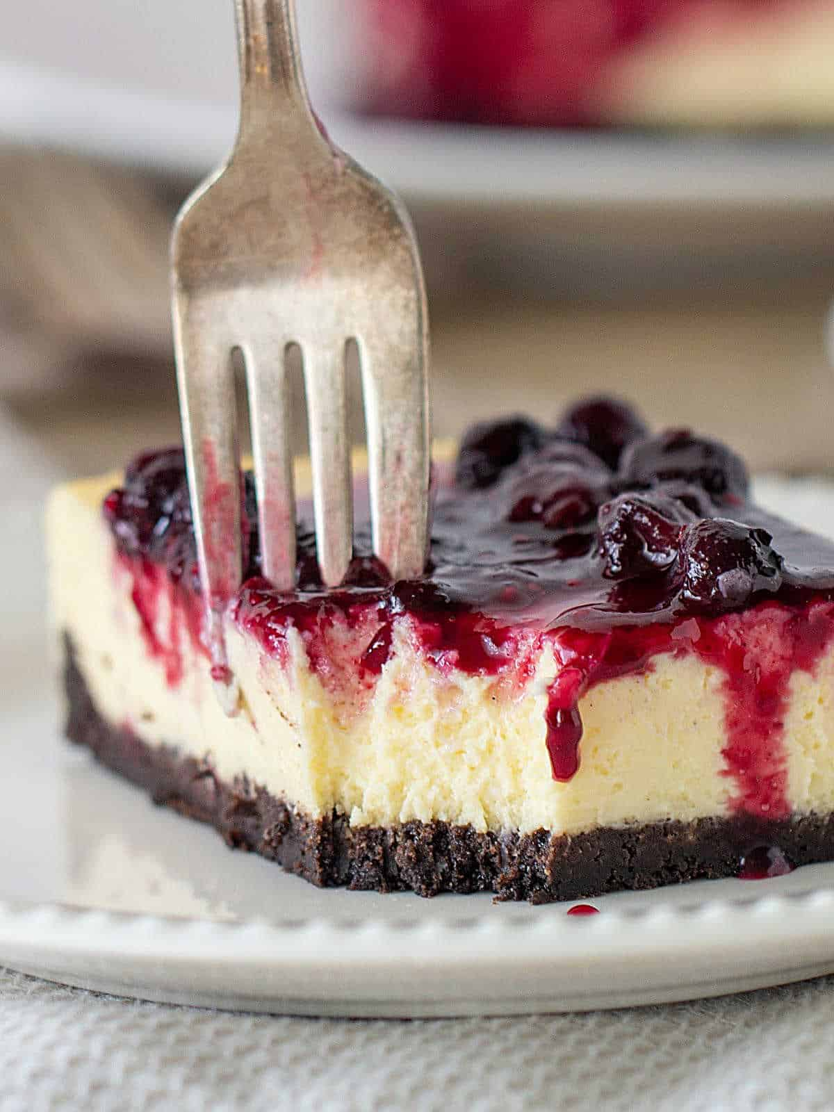 Close-up of cheesecake square on white plate, fork digging into it, berry topping