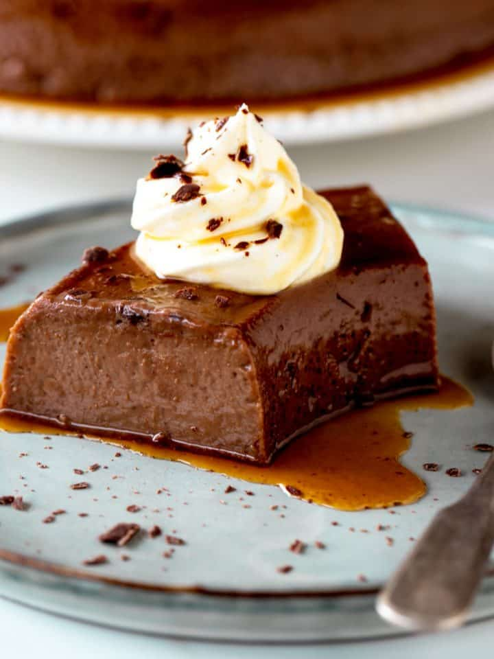 Grey plate with single serving of chocolate flan with dollop of cream and a silver spoon