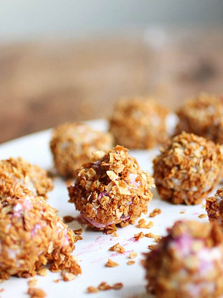 Ice cream truffles covered in granola on white plate