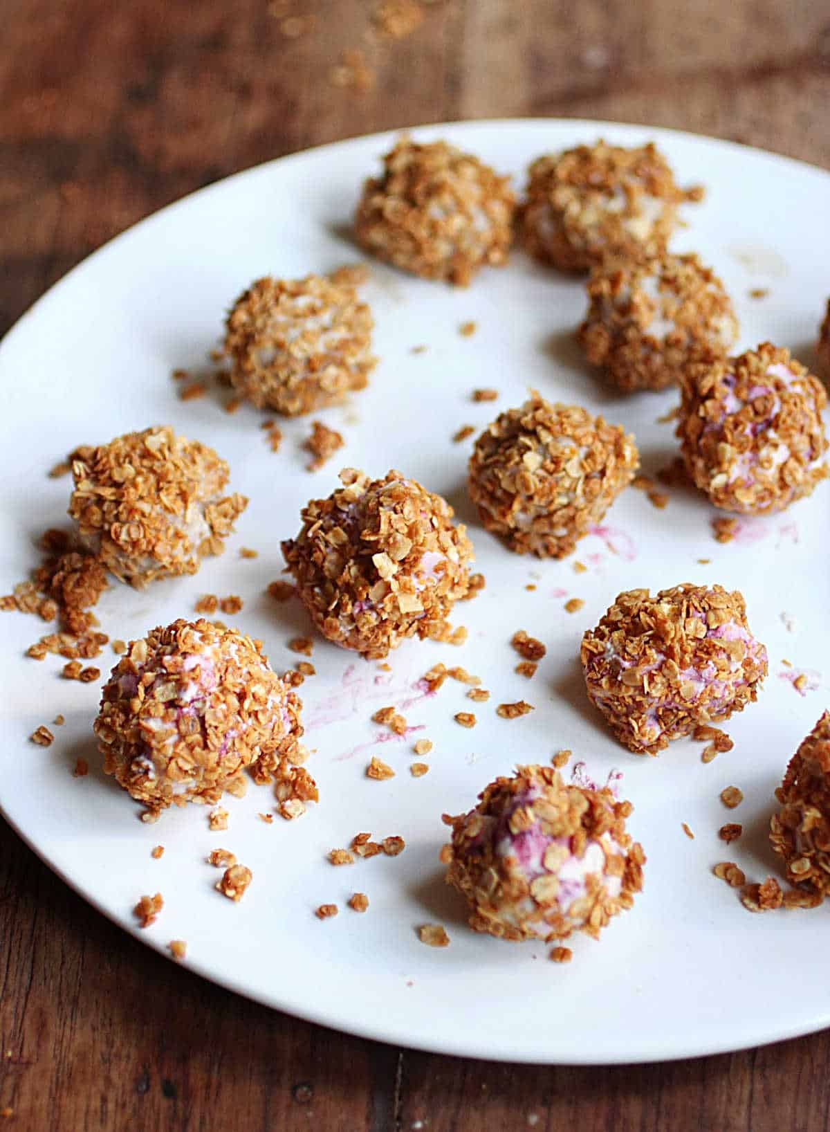 Small ice cream truffles covered in granola on white plate