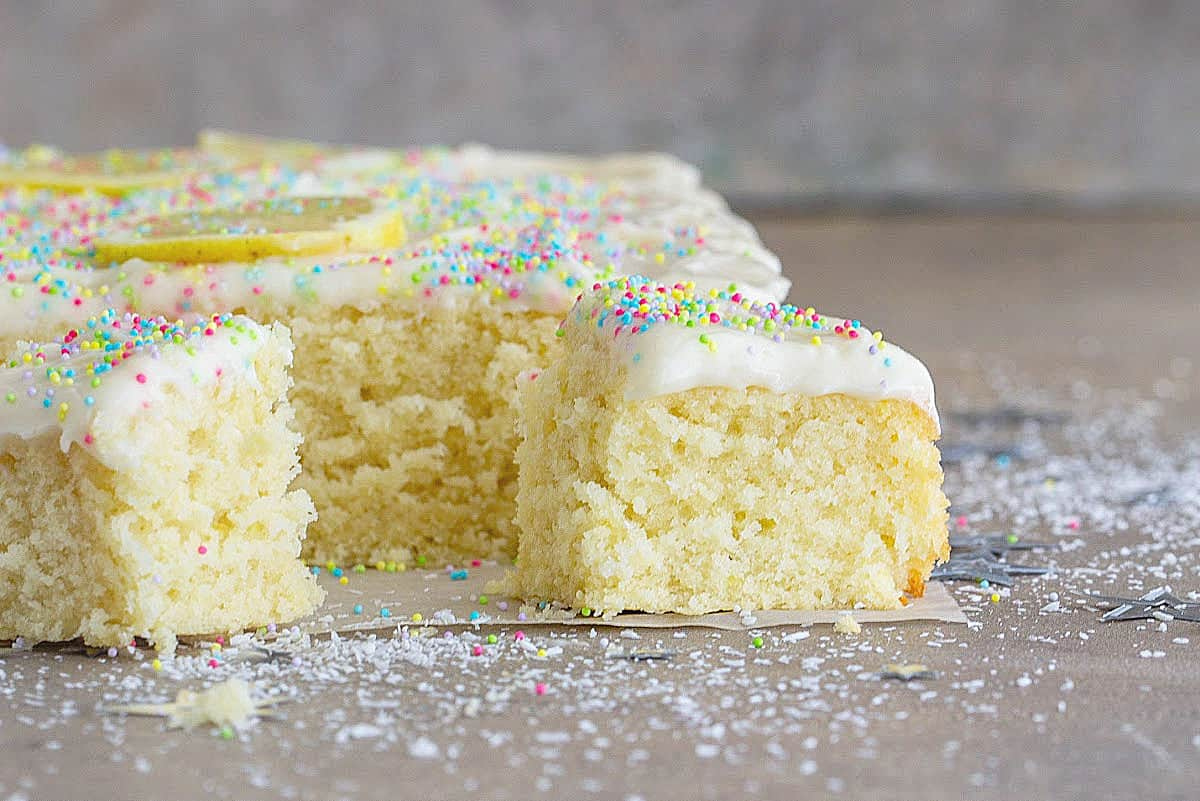 Frosted coconut sheet cake, cut squares on grey surface; sprikles, loose coconut