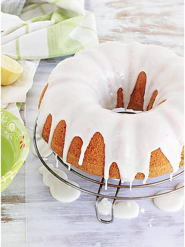 Glazed bundt cake on wire rack on white table, green props