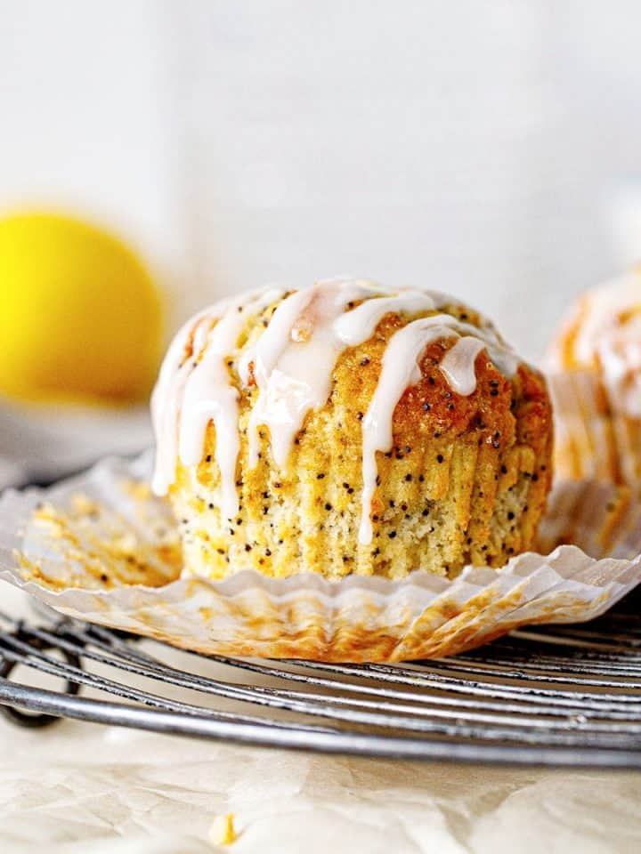 Wire rack with glazed lemon muffin in an open paper cup, white background