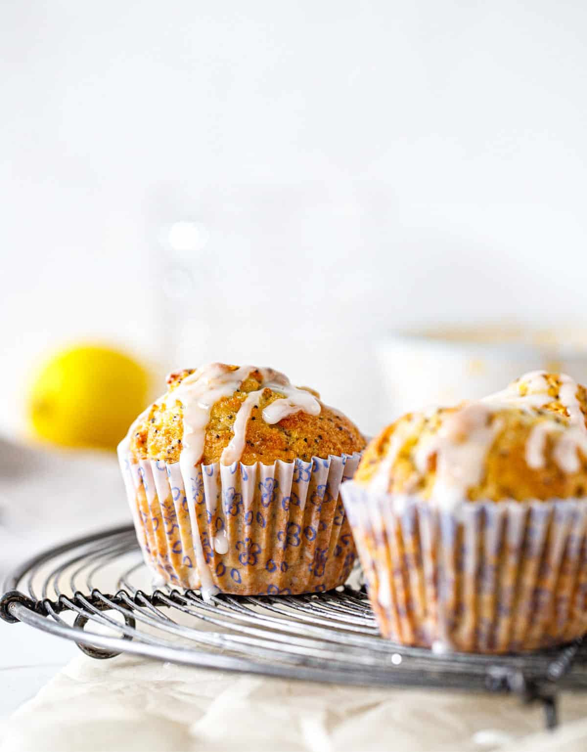 Two glazed lemon muffins on wire rack, a lemon in white background