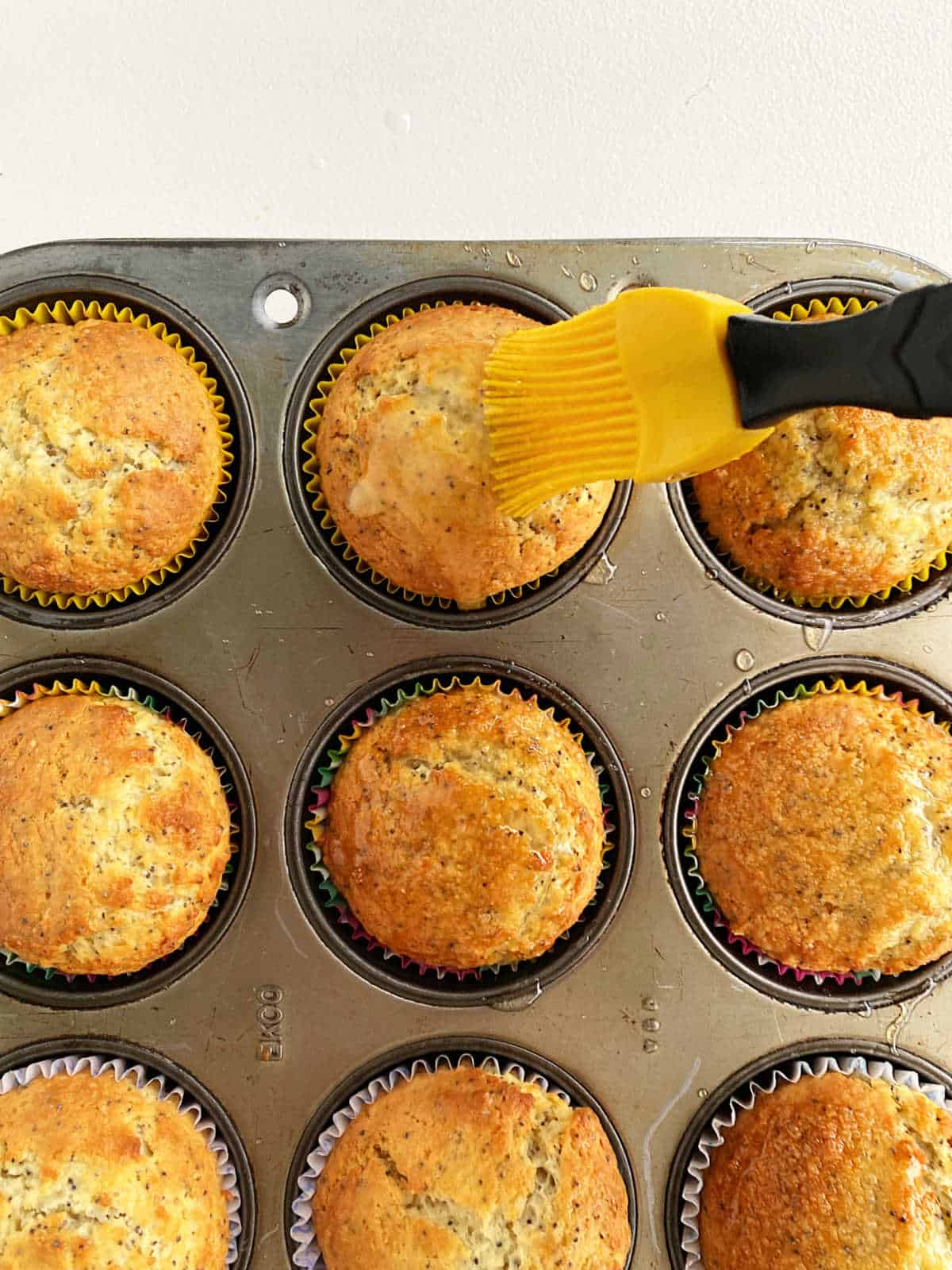 Brushing lemon muffins in metal pan with syrup