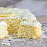 Grey surface with frosted coconut sheet cake, loose shredded coconut and confetti