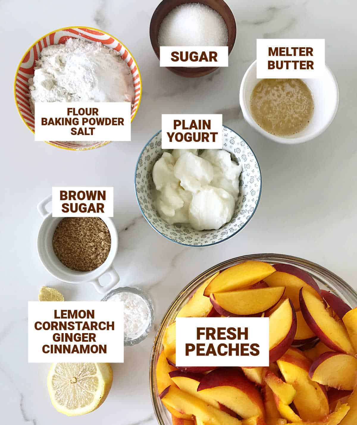 White surface with bowls containing ingredients for peach cobbler including yogurt, butter, lemon, and brown sugar