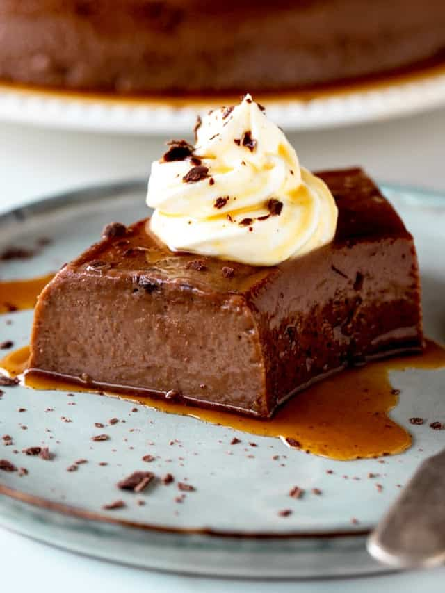 Cream topped serving of chocolate flan on grey blue plate with silver spoon
