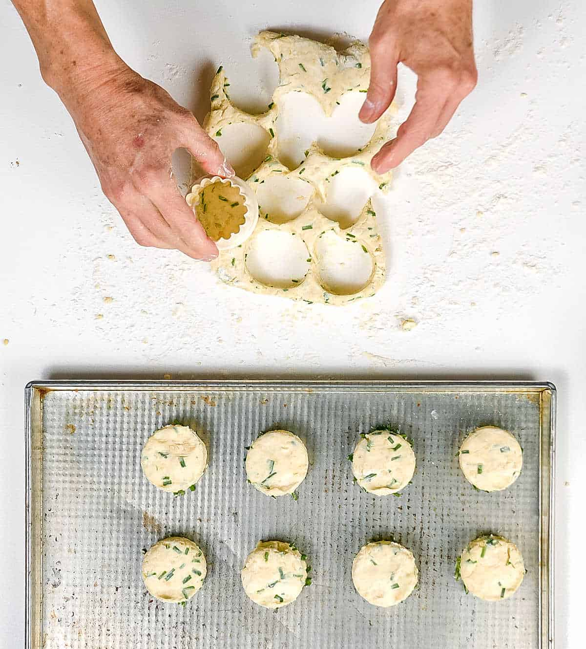 Top view of hand cutting scones and more on metal tray, white surface