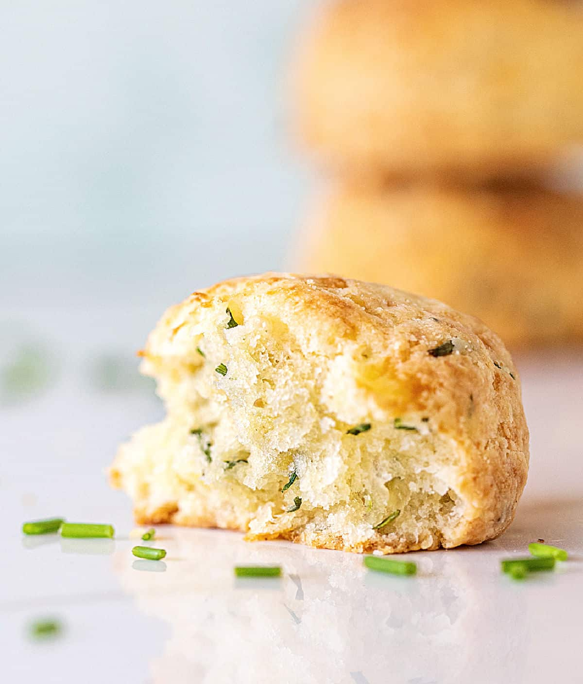 Half a scone on white surface, chopped chives around