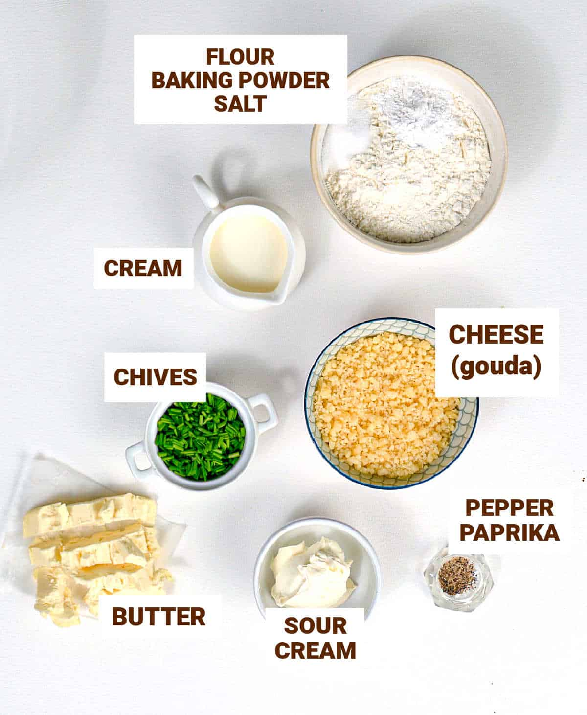 White surface with bowls containing ingredients for cheese scones including chives, butter, sour cream and flour