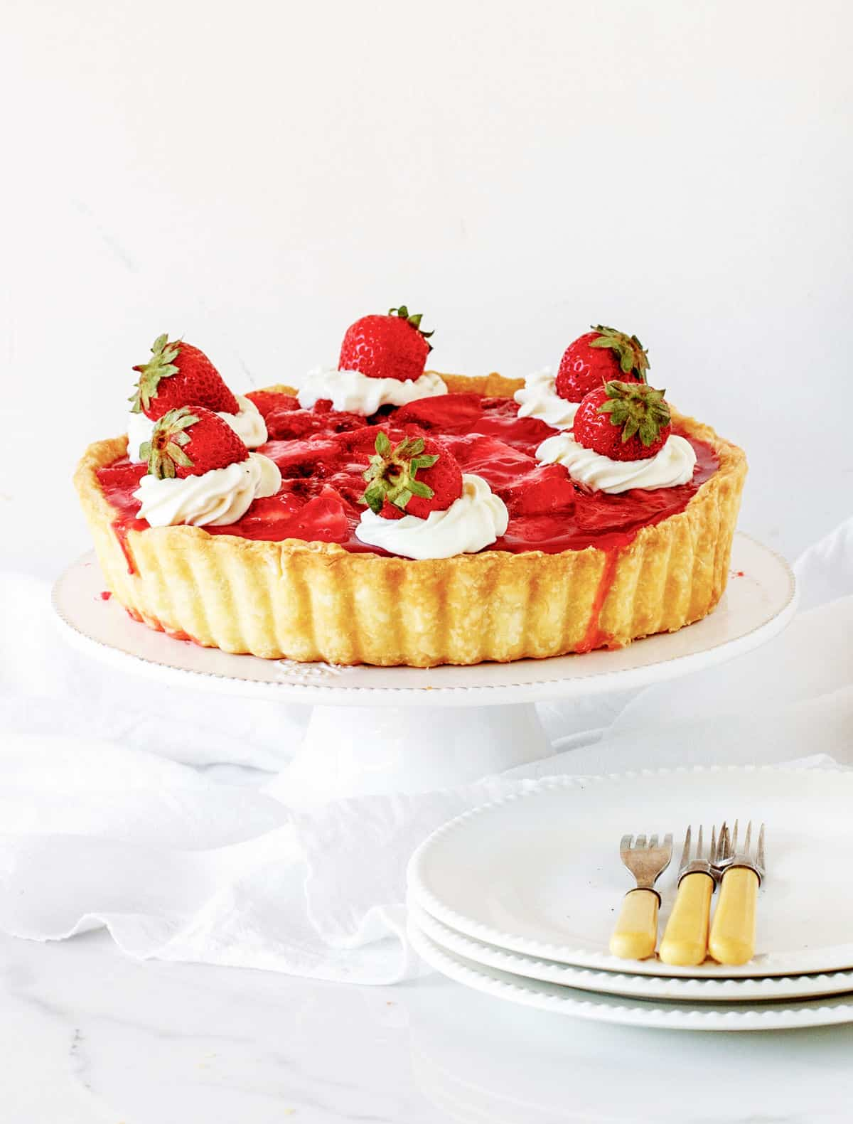 Whole strawberry pie on white cake stand, plates with forks, white background