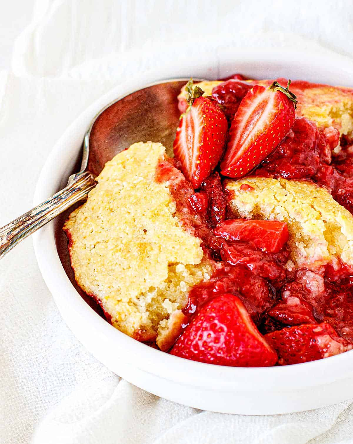 White bowl with strawberry cobbler serving, silver spoon, white background