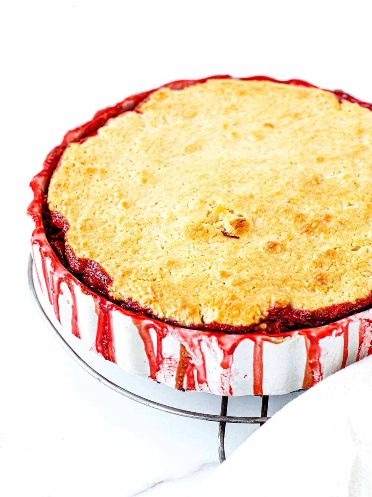 Partial view of round white dish with baked strawberry cobbler on white surface