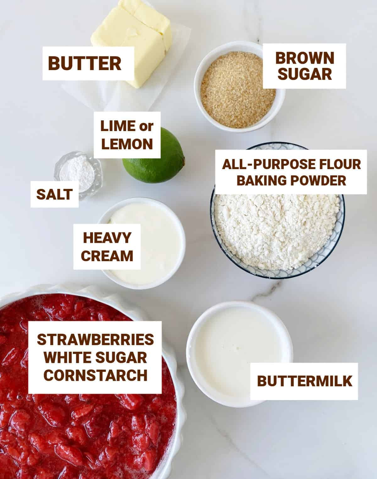Greyish surface with ingredients in bowls strawberry cobbler including lime, butter, brown sugar, buttermilk, cream