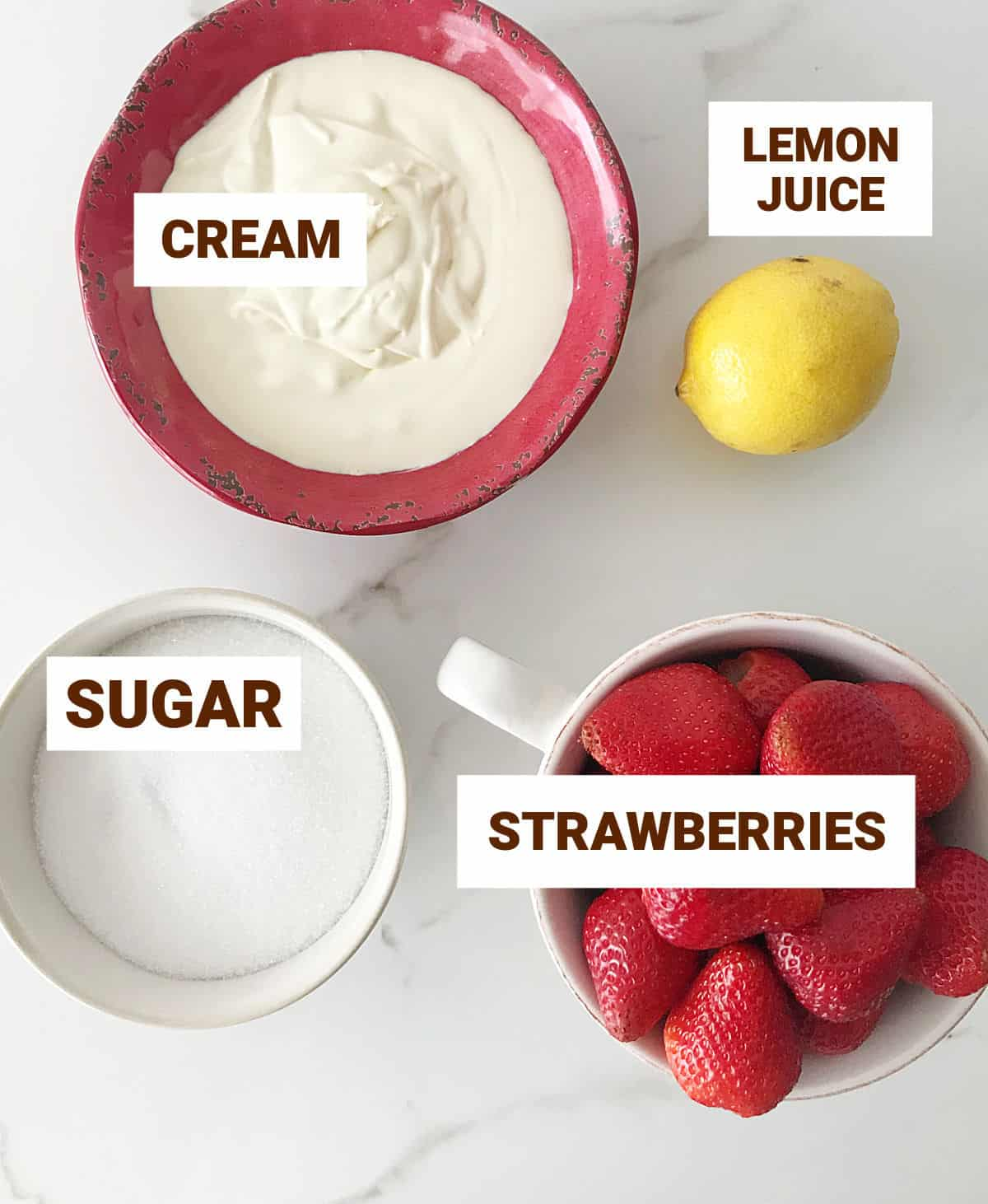 Ingredients for fresh strawberry ice cream on white surface, including lemon, cream, and sugar