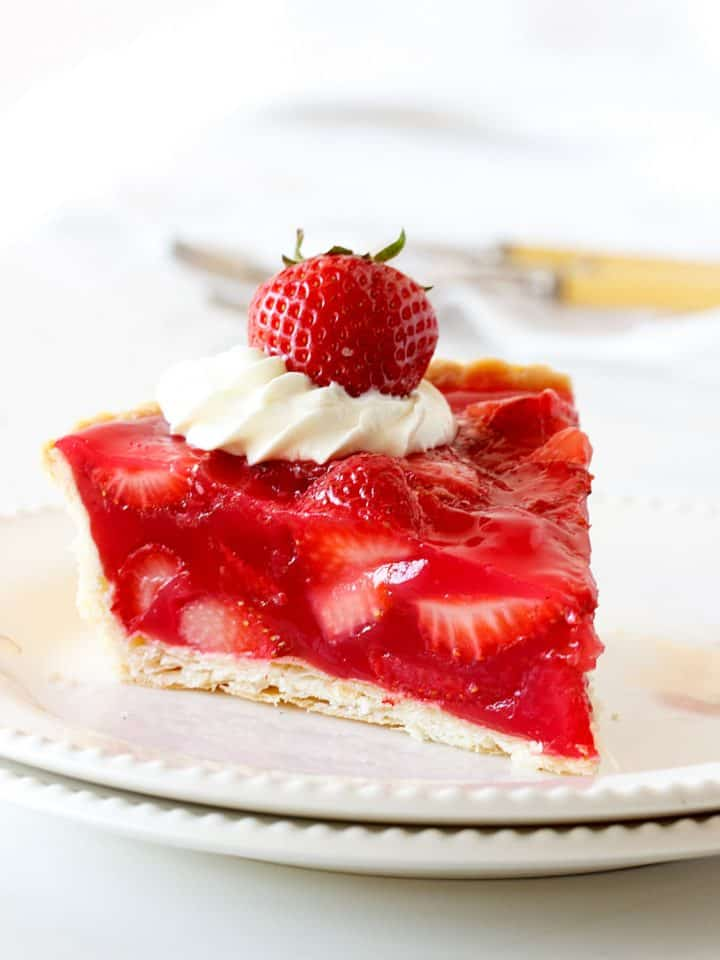 One slice of strawberry pie on two white plates