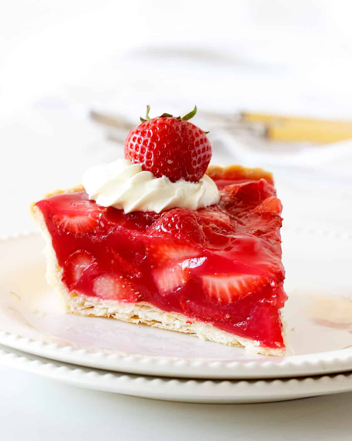 A slice of fresh strawberry pie on white plate with white background