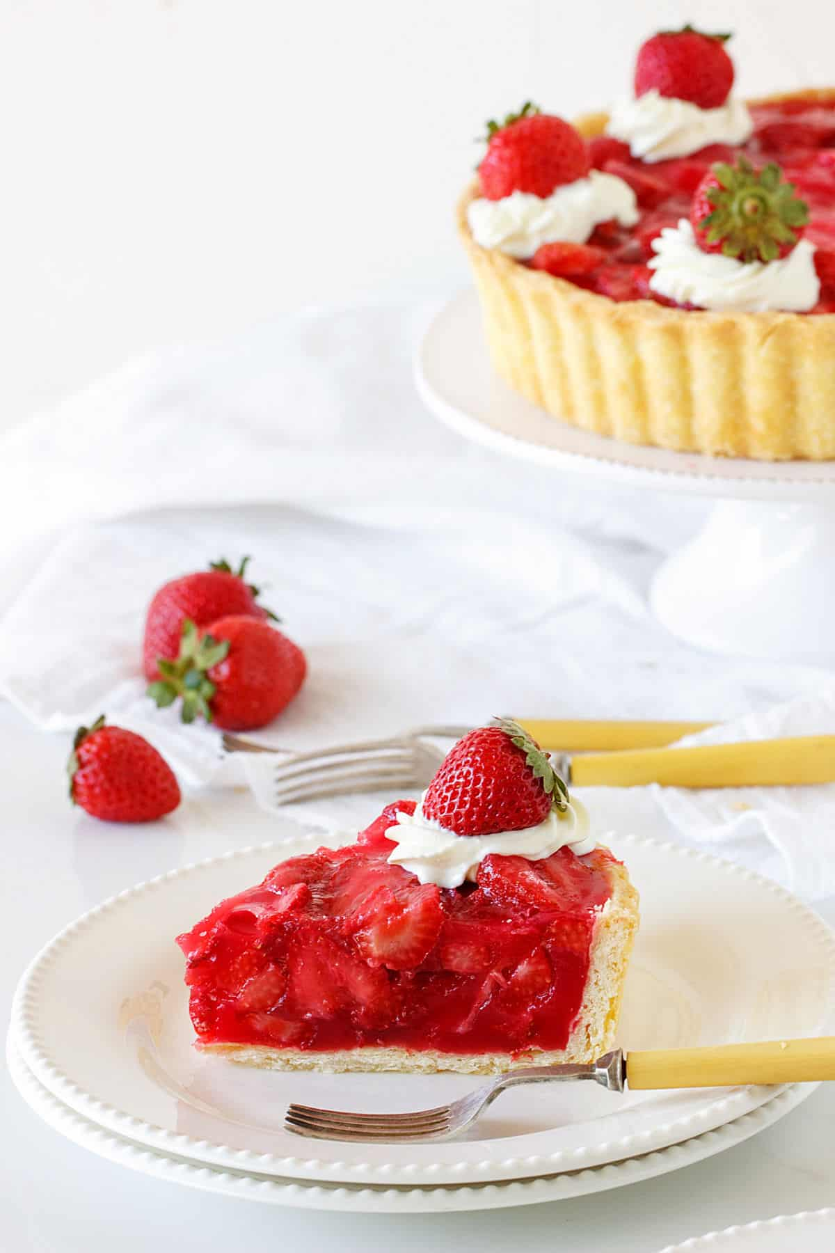 White background with partial strawberry pie on cake stand, single slice on white plate in front
