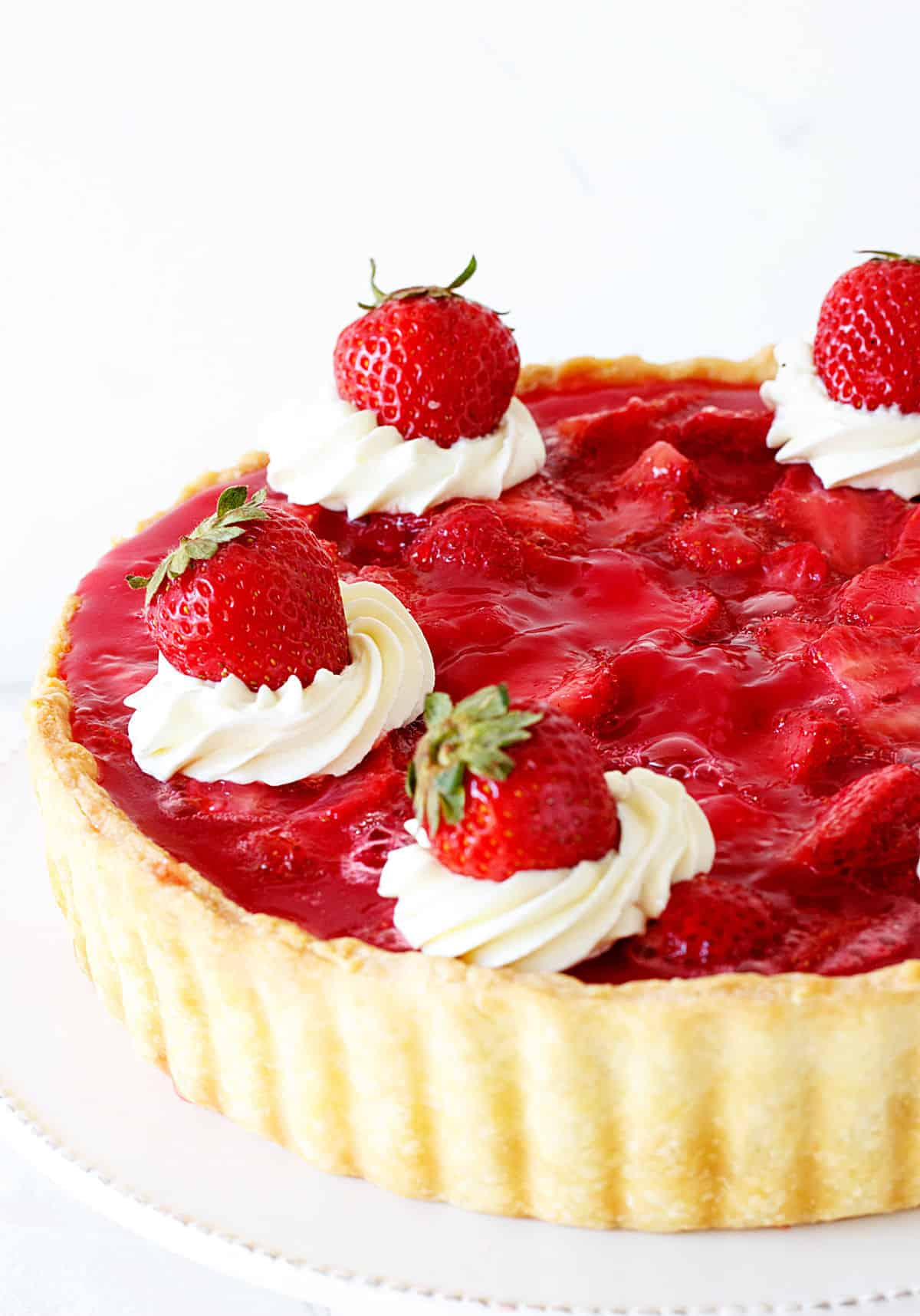 Half strawberry tart with piped cream on top on white background
