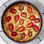 Top view of baked tomato focaccia on round pan on wire rack, grey surface