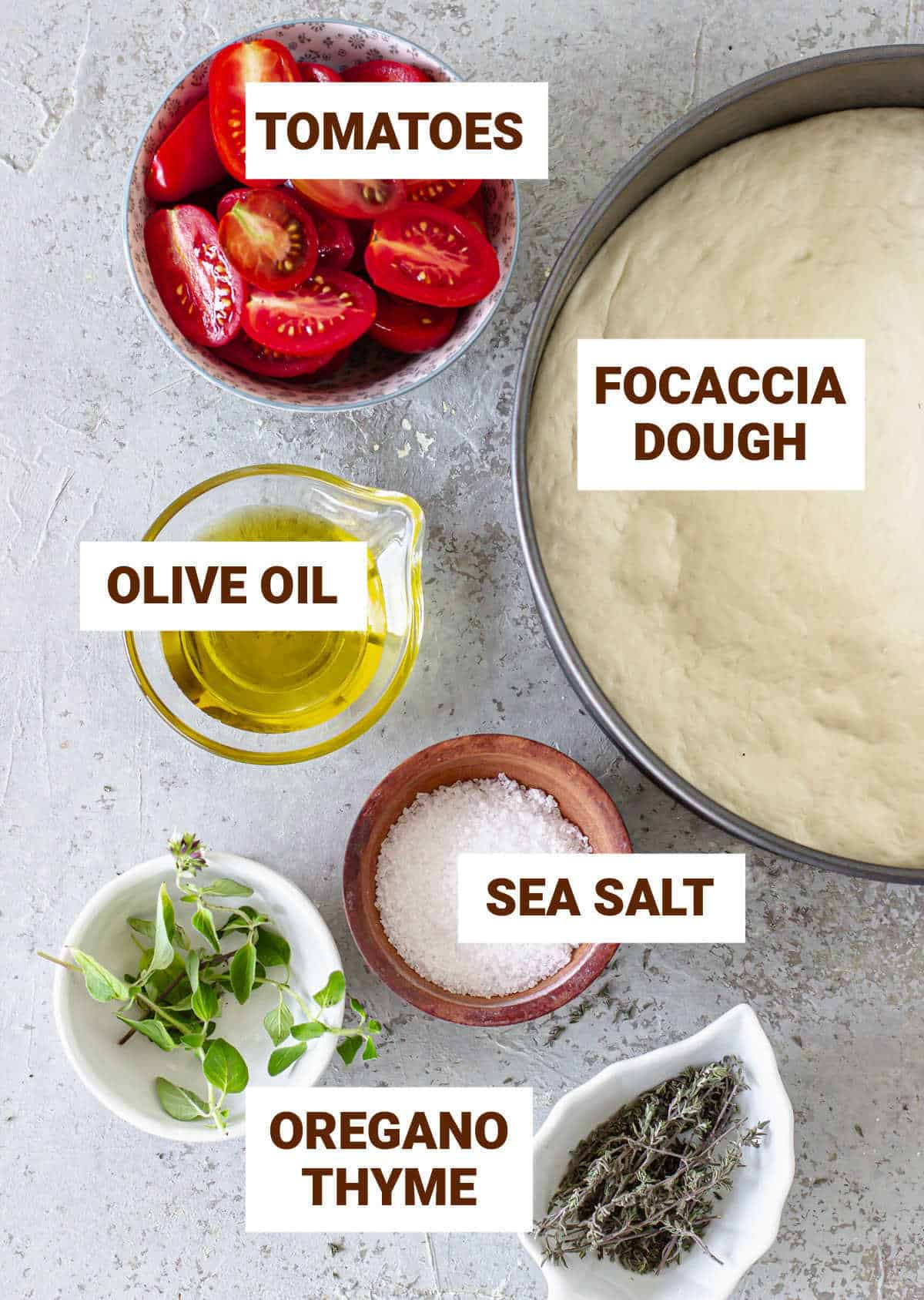 Grey surface with ingredients for tomato focaccia including dough, oil, salt and herbs