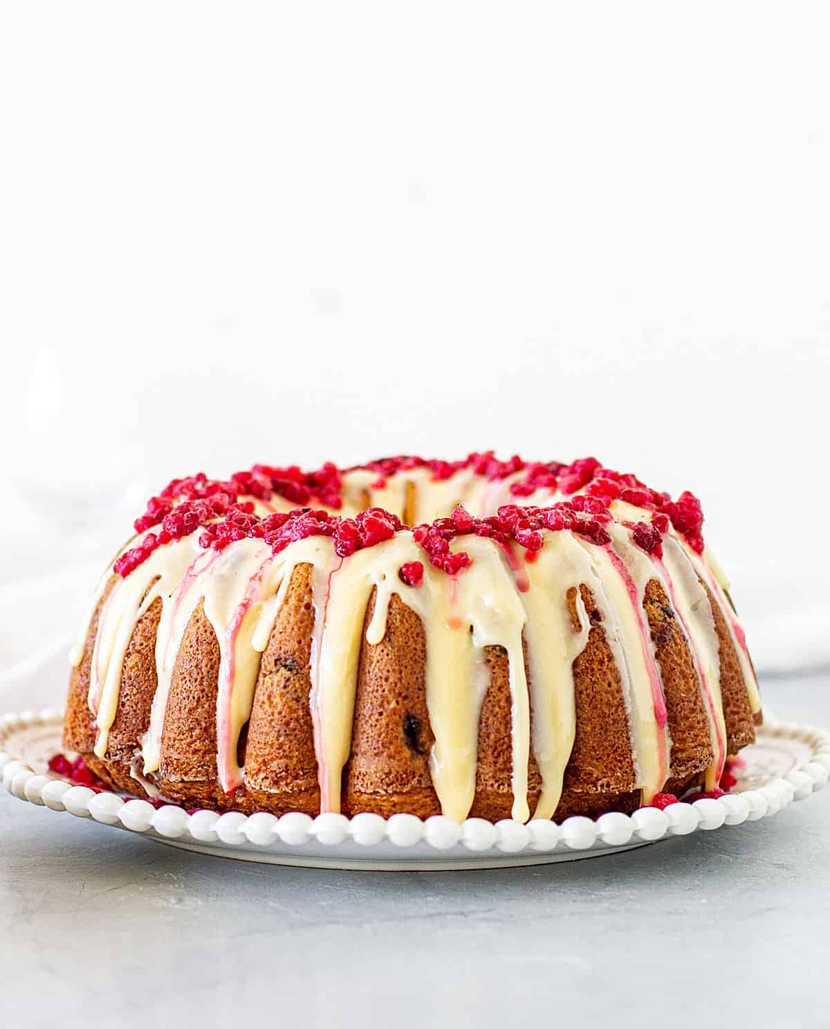 Whole bundt cake with white chocolate and raspberries on white plate, grey white background