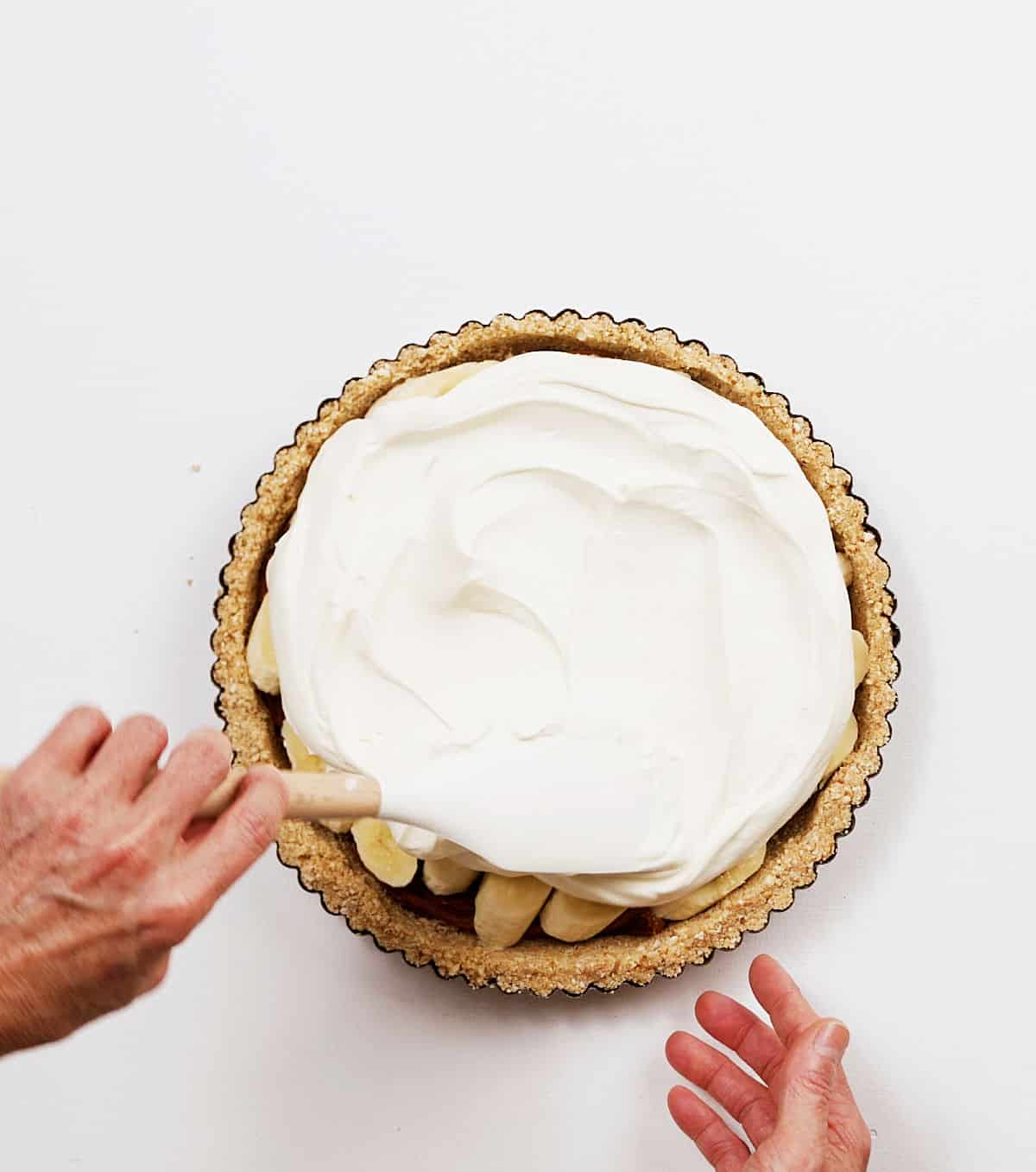 Overview of hands spreading whipped cream on pie, white surface