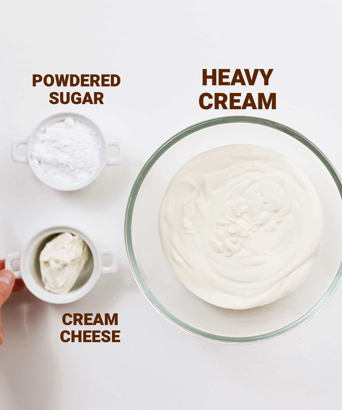 Three bowls with cream, powdered sugar and cream cheese on white surface