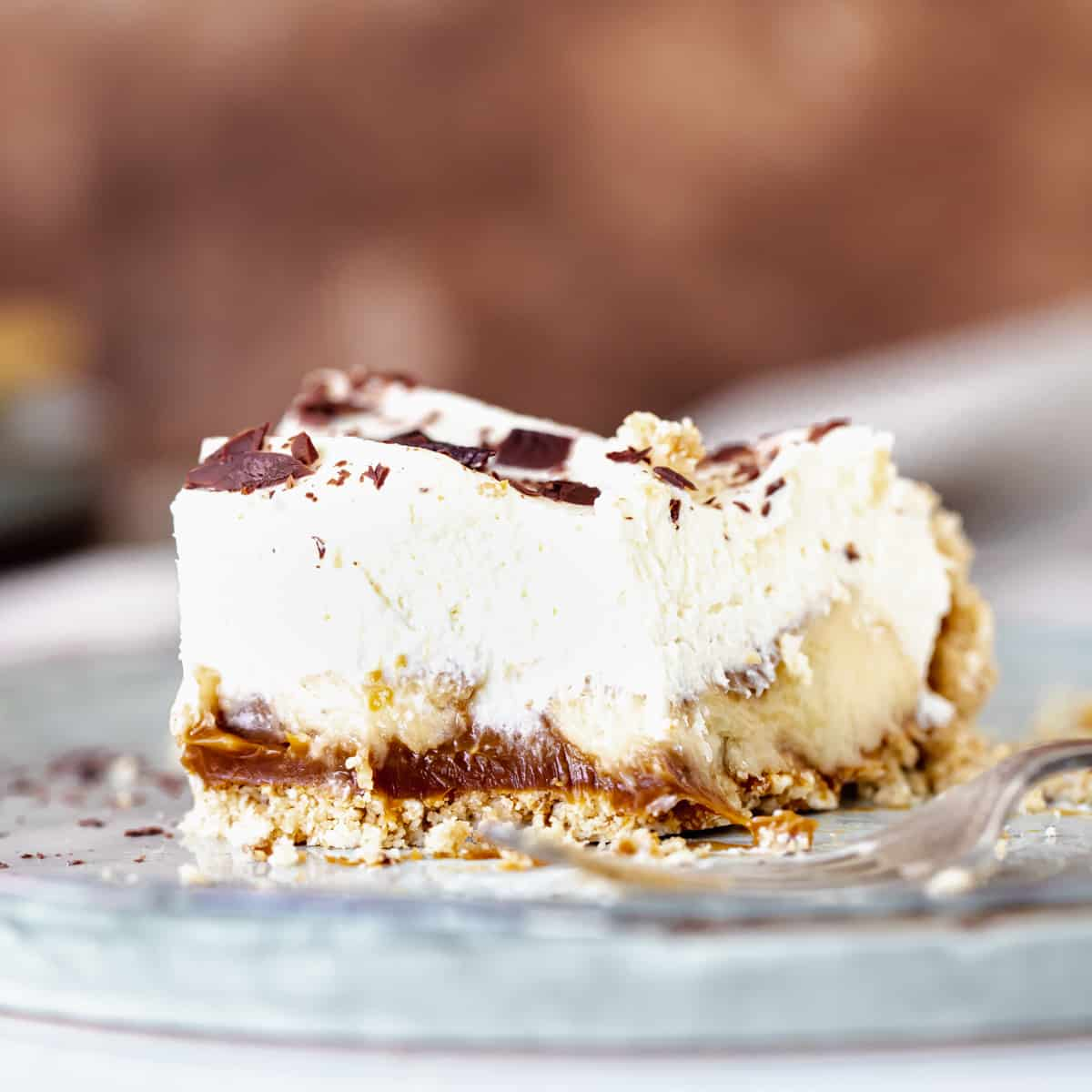 Straight on view of eaten slice of creamy banoffee pie on grey plate, brown background