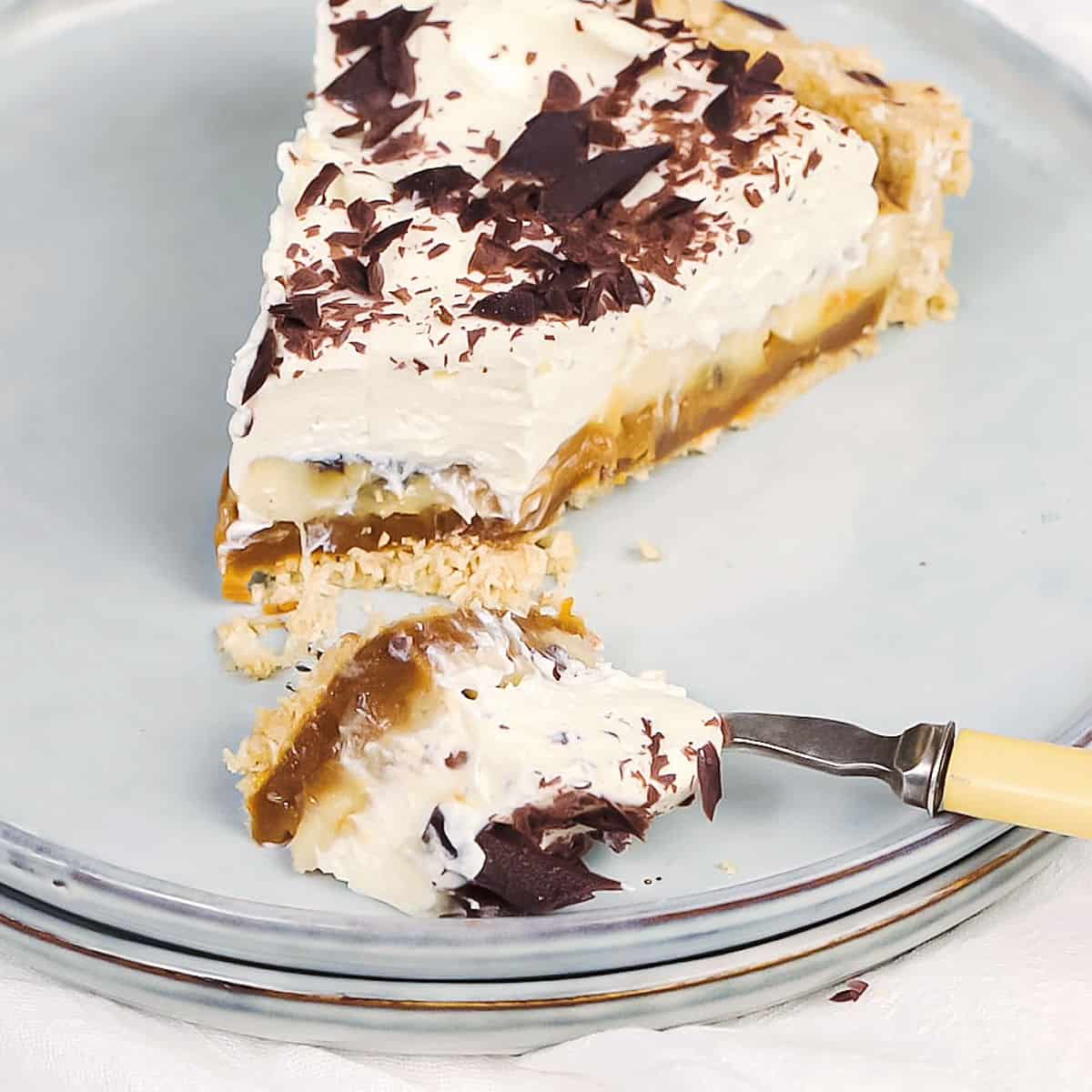 Close up of grey plate with slice of banoffee pie with fork