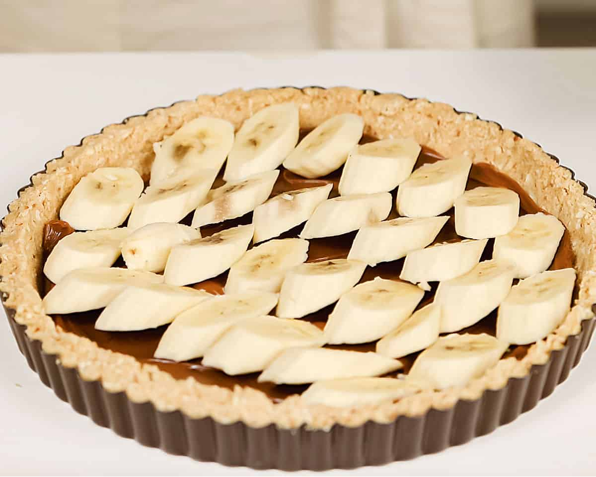 Cookie crust in pie pan with dulce de leche and sliced bananas, white surface