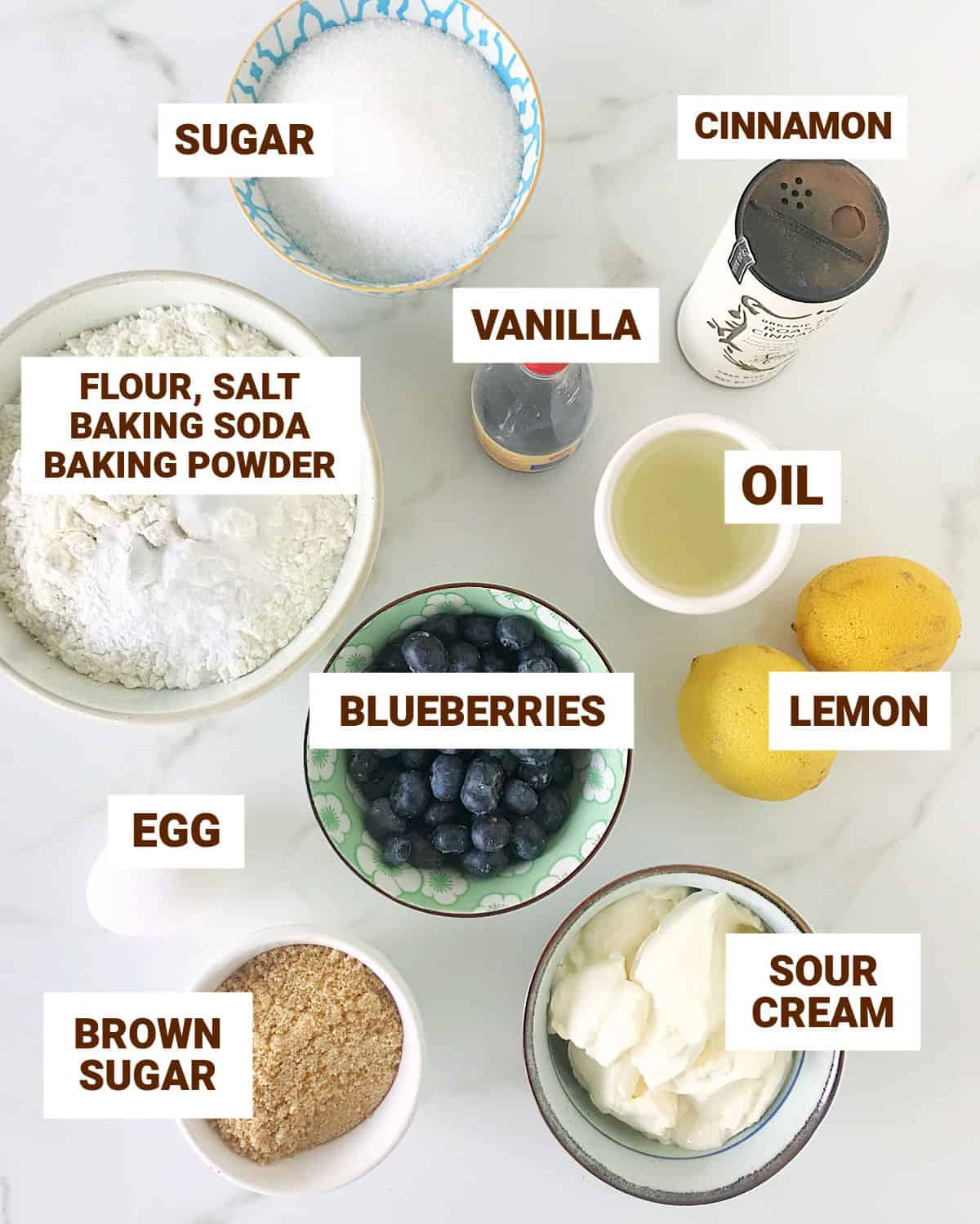 White surface with bowl containing ingredients for lemon blueberry cake including egg, brown sugar, cinnamon, oil, vanilla