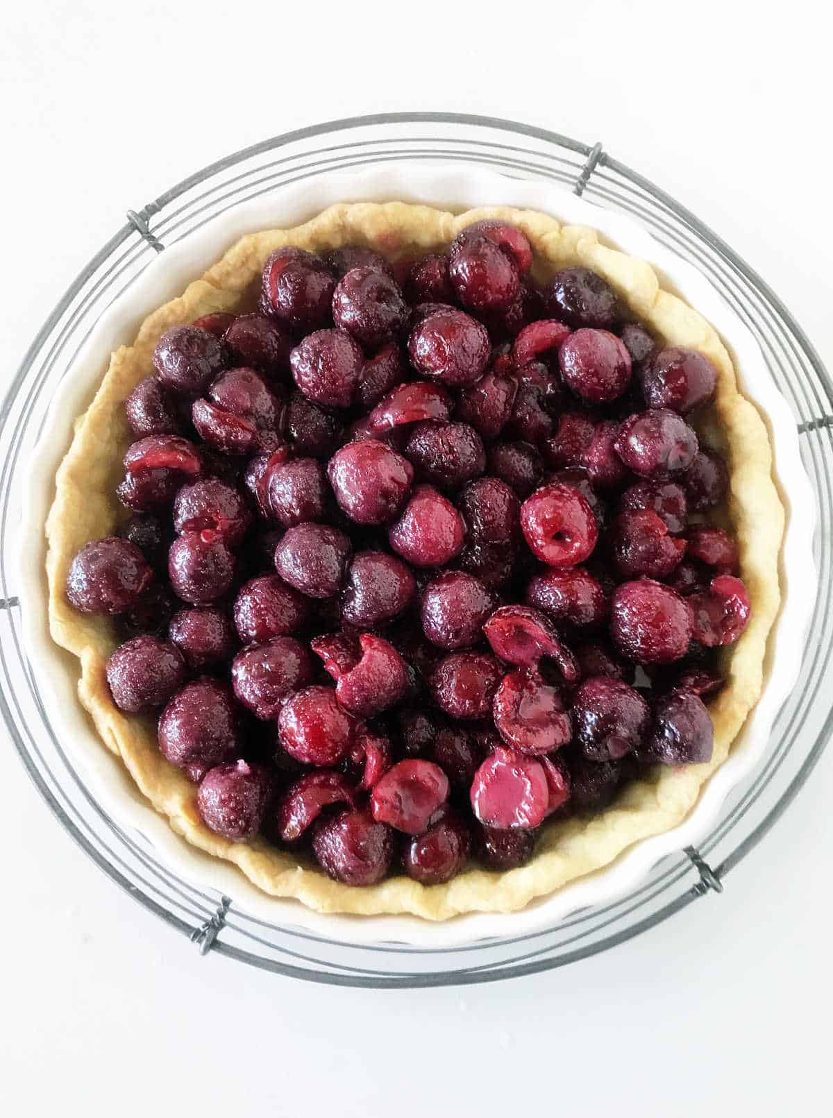Cherry filled pie crust on wire rack, white background