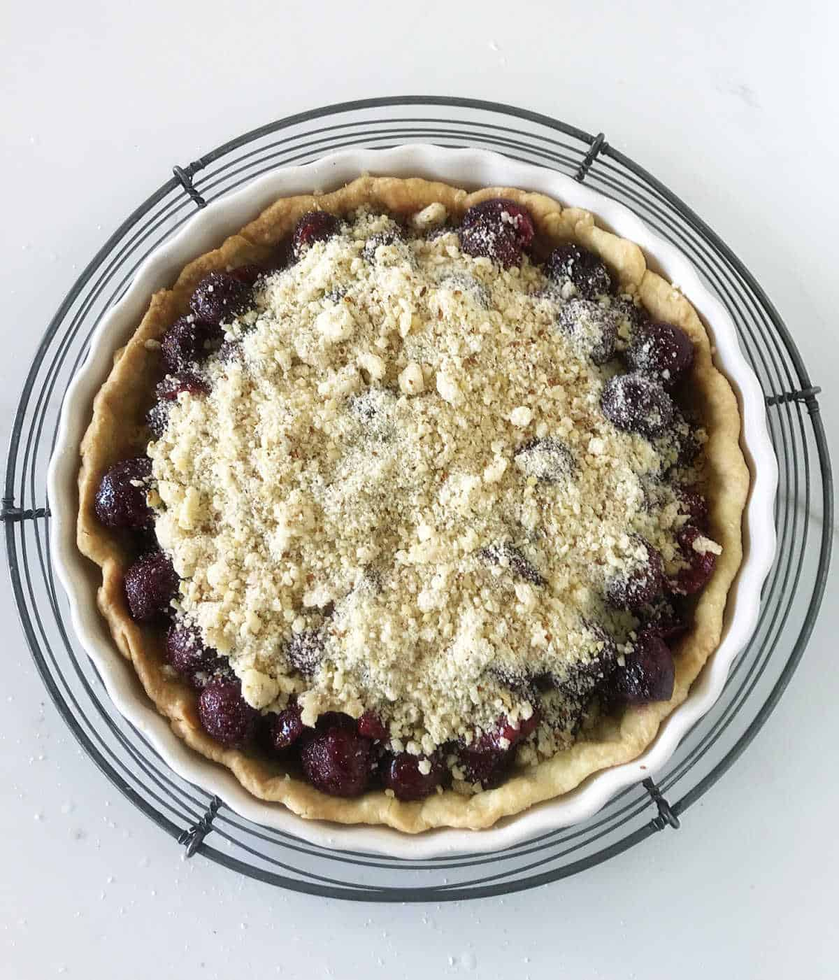 Over view of unbaked cherry crumb pie on wire rack on white surface