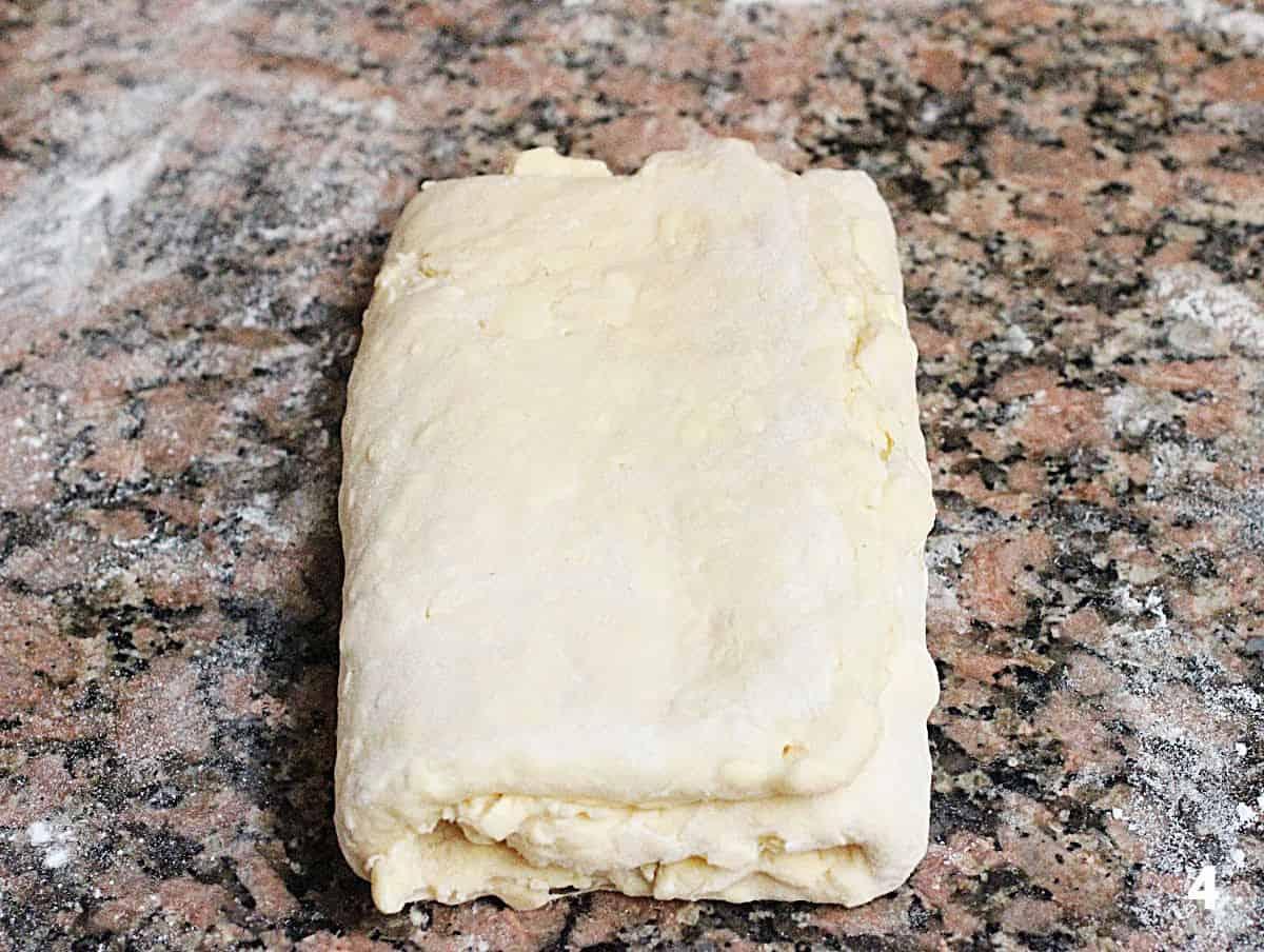 Rectangular block of danish pastry on floured brownish marble counter