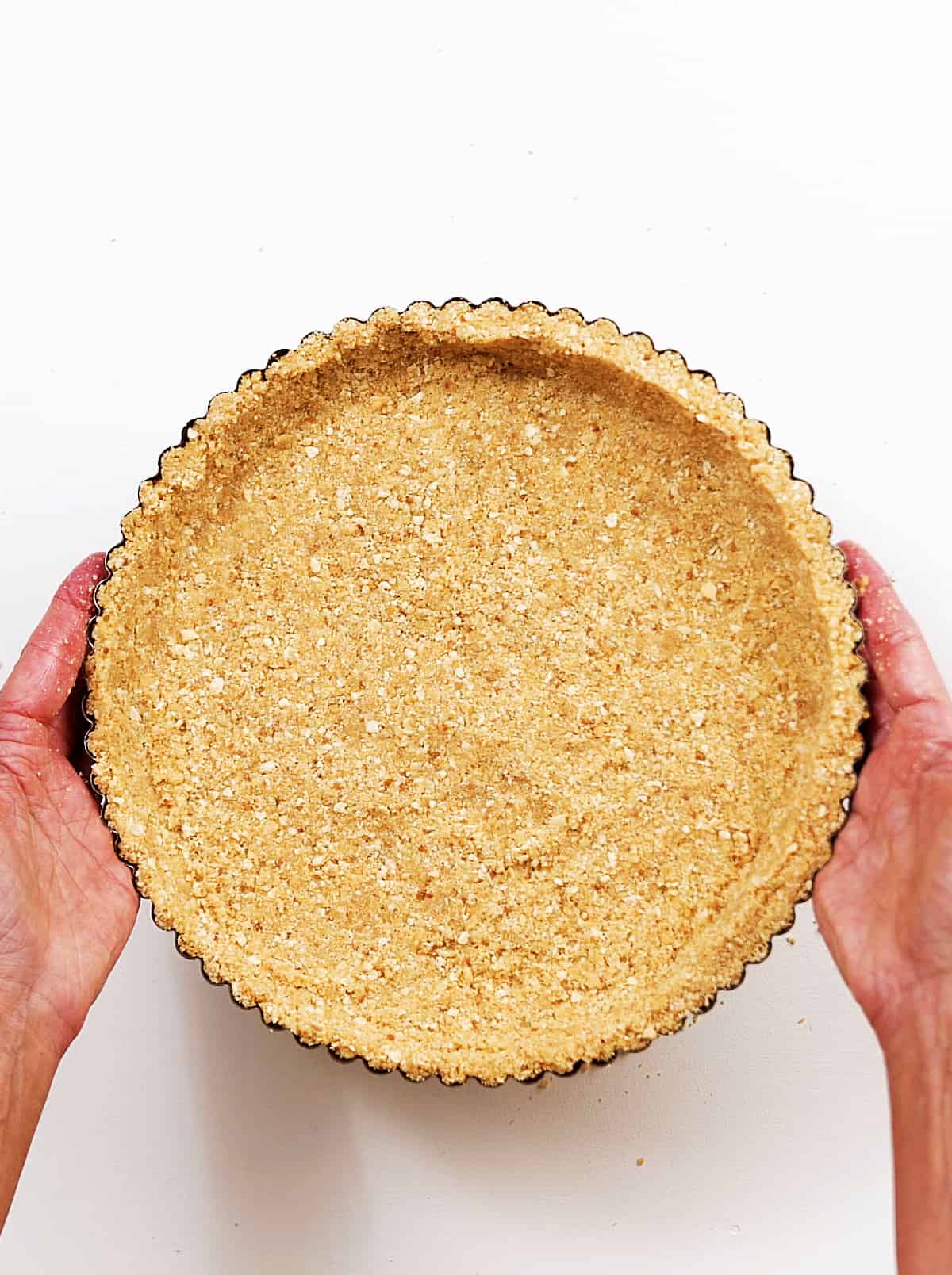 Top view of hands holding graham cracker crust on white surface