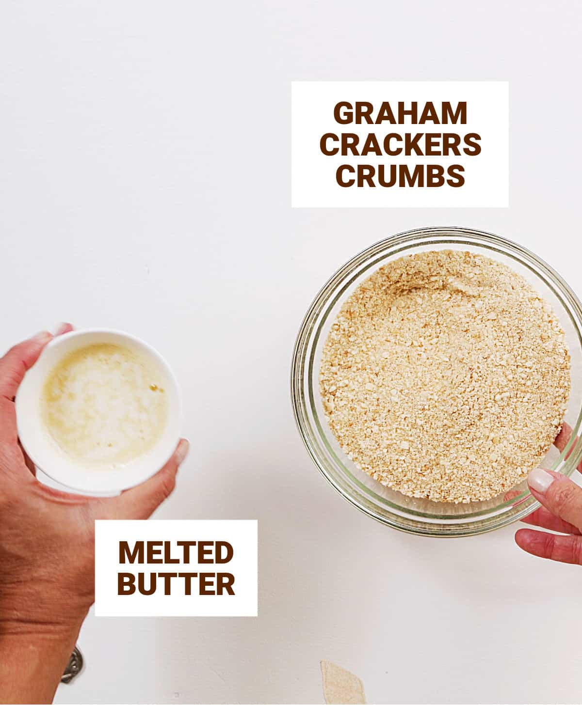 Overview of white surface with bowl containing cookie crumbs and hand holding cup with melted butter