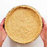 Hands holding round graham cracker crust on a white surface