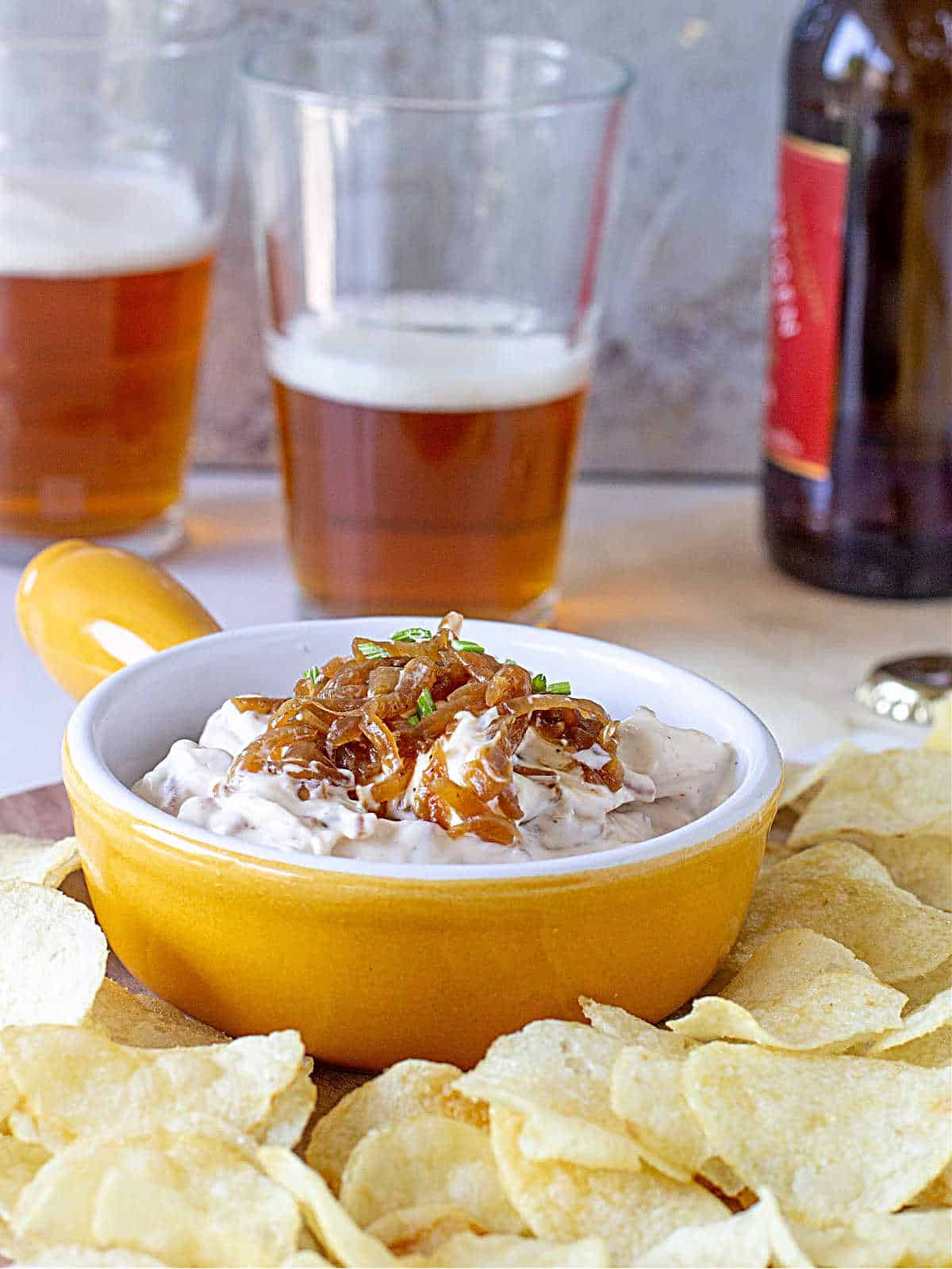Caramelized Onion Dip in yellow ramekin surrounded by potato chips and beer