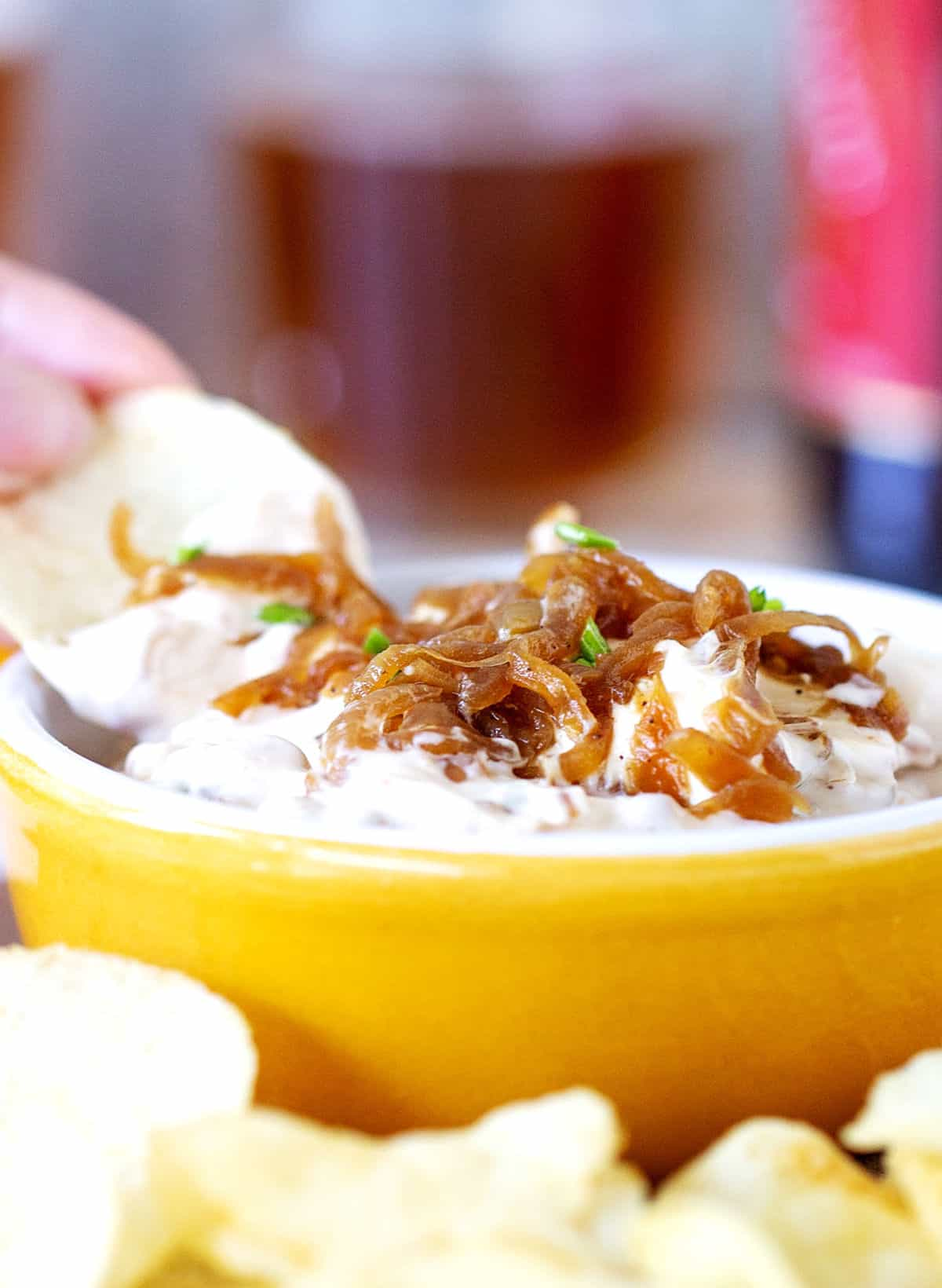 Potato chips and beer surrounding yellow ramekin with onion dip
