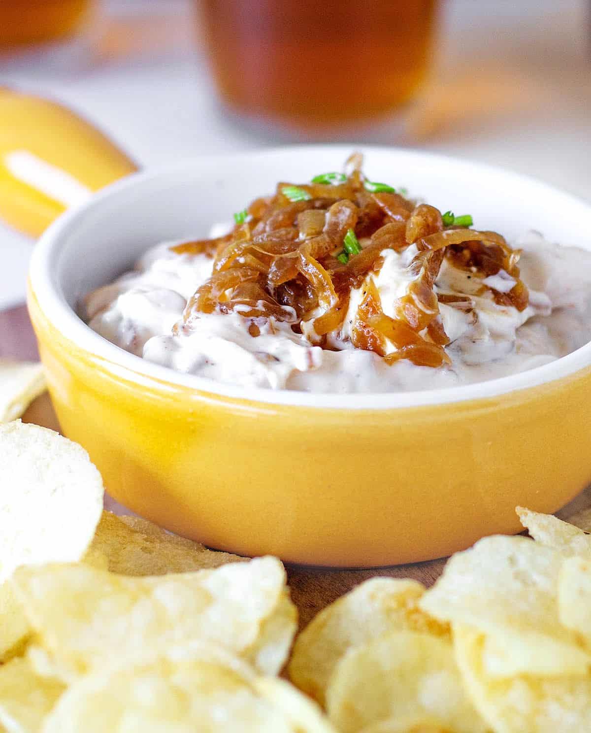 Shallow yellow bowl with onion dip, potato chips around