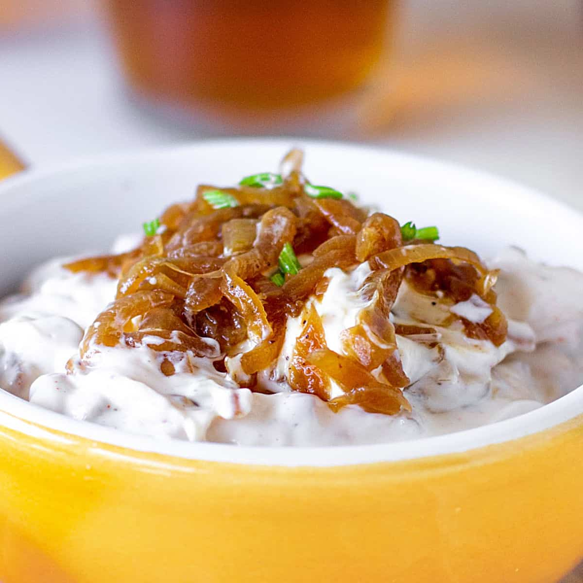 Close up of caramelized onion dip in yellow bowl