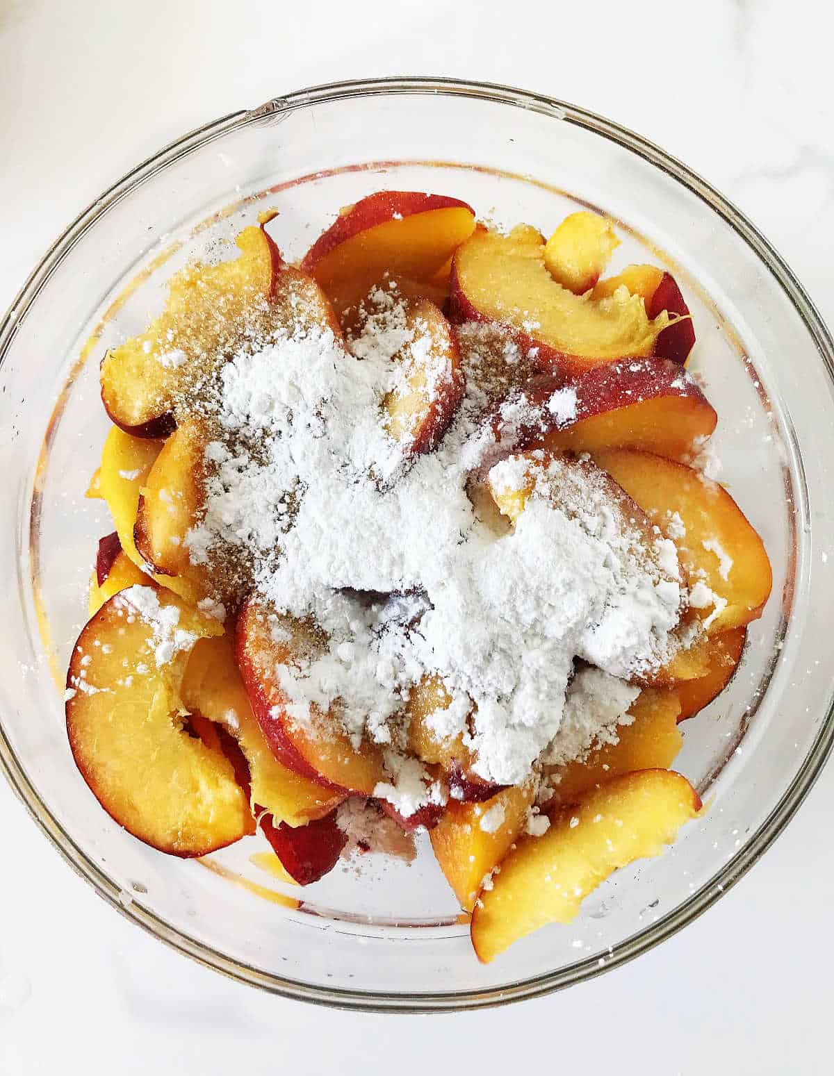 Glass bowl with peaches and cornstarch on white surface