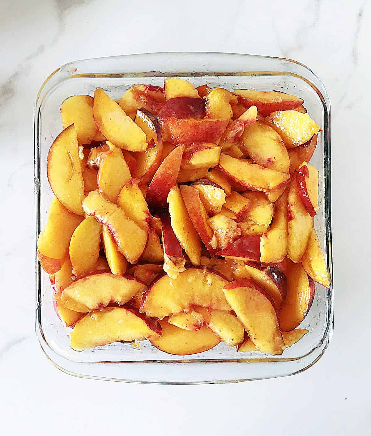 Square glass dish with sliced peaches on marble counter