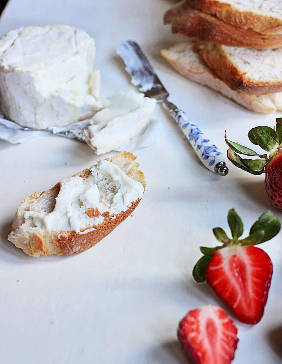 White table with cheese, knife, bread slices, fresh strawberries