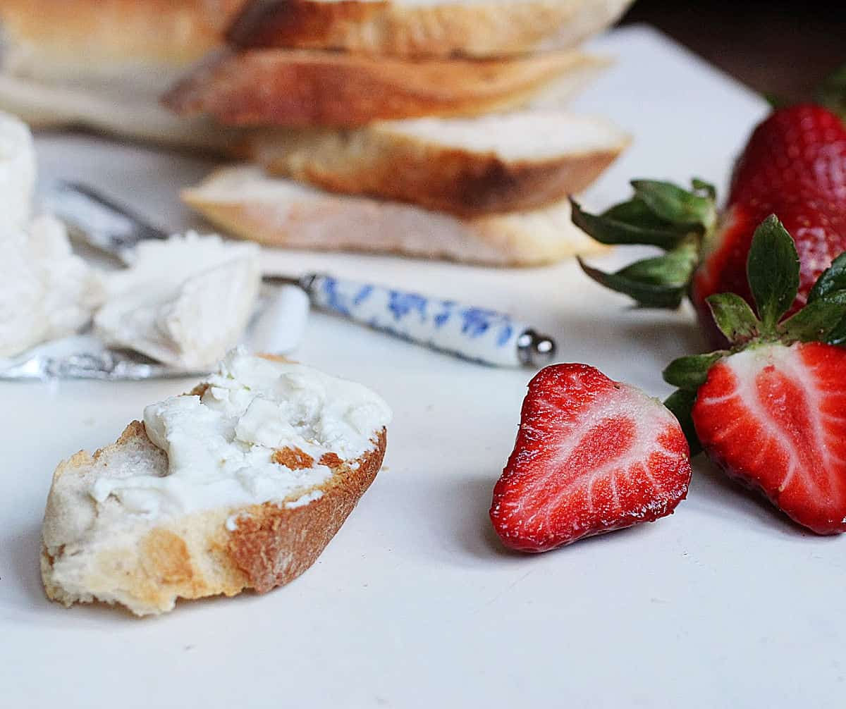 Slicce of bread with cheese, stack of bread slices, cut fresh strawberries, all on white surface