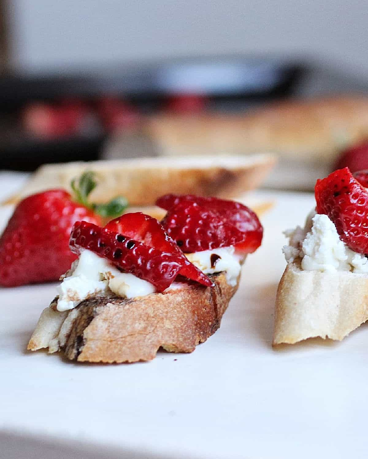 Slices of bread with cheese and strawberries on white table
