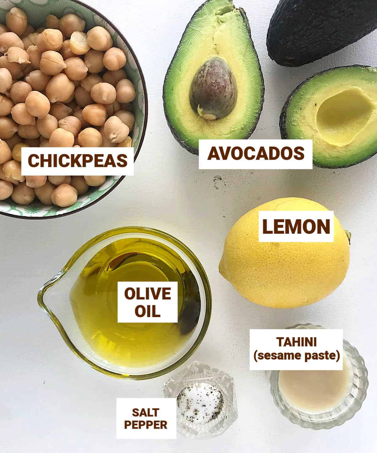 Ingredients for avocado hummus , in bowls on white surface, including lemon, chickpeas, oil, tahini