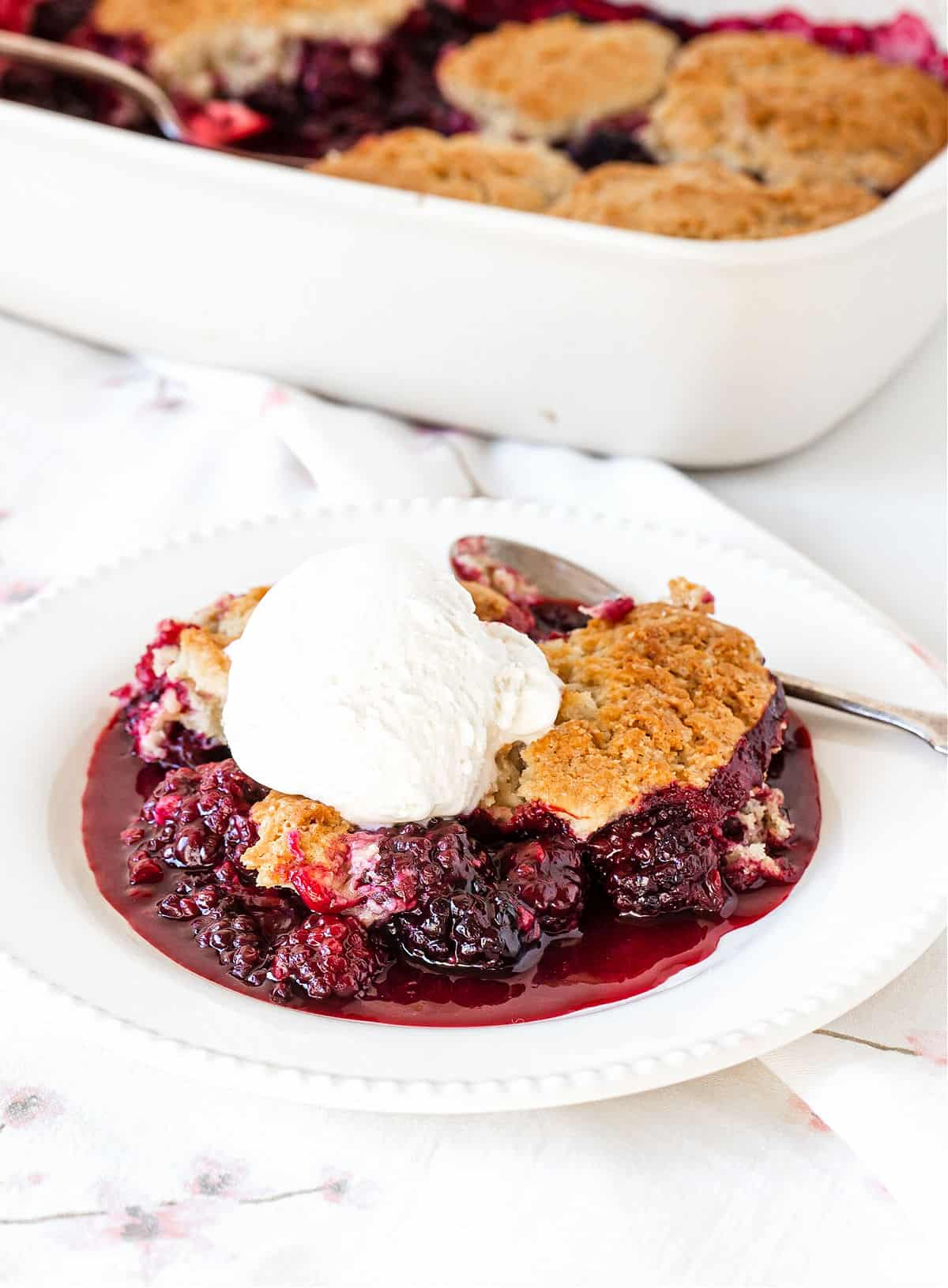 A serving of blackberry cobbler with ice cream on white plate and background